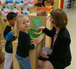 Beverly Hunter, Greenville program manager for the ABC Program of the S.C. Department of Social Services, helps children fill their toy shopping basket with plastic fruits and vegetables.