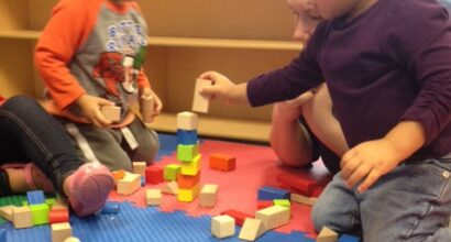 Practicing stacking blocks in the one-year-old classroom